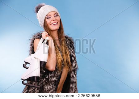 Winter Sport Activity Concept. Woman Wearing Furry Warm Hat Holding Ice Skate, Blue Background Studi