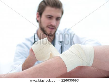 doctor bandaging a wound on the leg of the patient