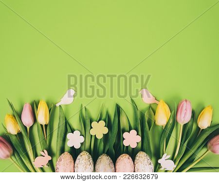Creative Easter Composition With Painted Eggs Against Green Background With Space For Your Text.