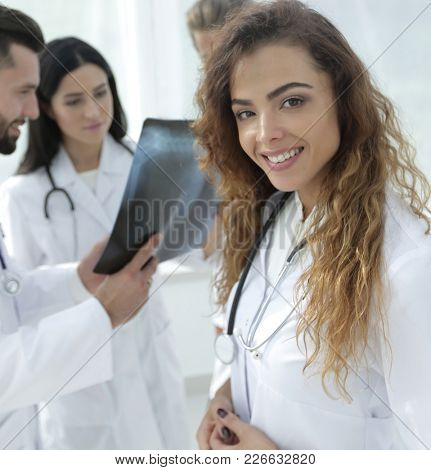 confident doctors in hospital looking at x-ray.