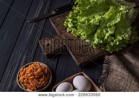 Salad, Carrots, Eggs, Knife, Board, Tablecloth On A Black Wooden Table