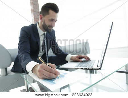finance manager working with business graphics on a laptop