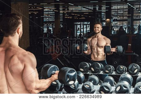 Good Looking Young Man Lifting Dumbbells And Working On His Biceps In Front Of The Mirror Doing Exer