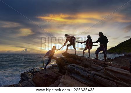 Male And Female Hikers Climbing Up Silhouette Mountain Cliff And One Of Them Giving Helping Hand. Pe