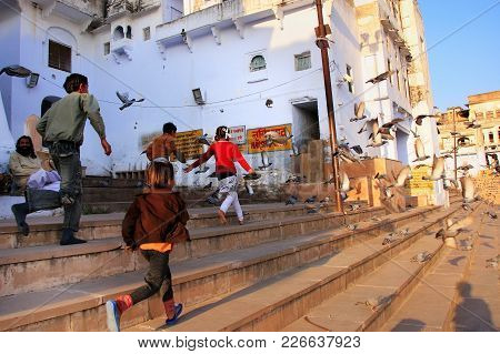 Pushkar, India - February 23: Unidentified Kids Chase Pigeons Near Holy Lake On February 23, 2011 In