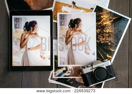 Printed Wedding Photos With The Bride, A Vintage Black Camera And A Black Tablet With A Picture Of B