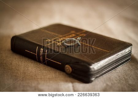 Picture Of A Book Bible Close-up In Black Leather Binding With A Zipper With A Christian Pendant Sym