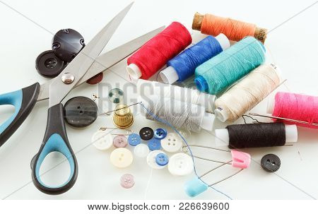 Photo Of Multi-colored Threads And Buttons On A White Table Close-up