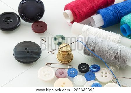 Photo Of Needle With Thread And Buttons On A Table Close-up