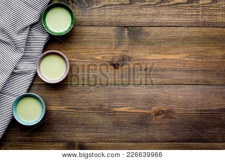 Make Matcha Tea. Matcha Tea In Small Cups Ready To Drink On Dark Wooden Background Top View.