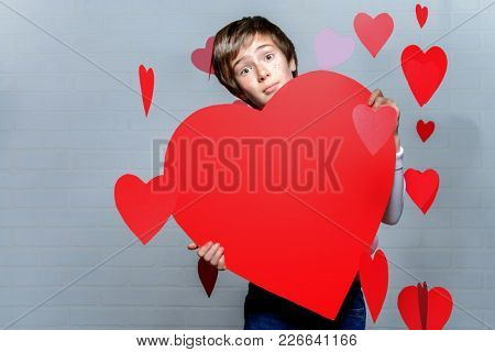 Ð¡ute child boy holding big heart surrounded by little hearts. First love. Valentine's Day.