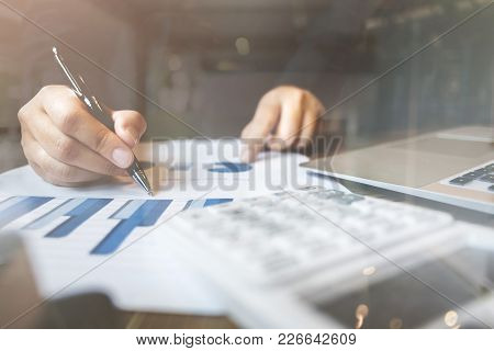 Bookkeeper /  Financial Inspector Calculating On Investment Data With Documents And Laptop In Dark O