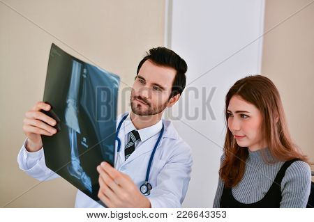 Health Concepts. Doctor And Patient Viewing X-ray Film. The Doctor And The Patient Feel Relaxed At T
