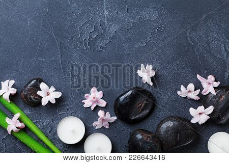 Spa Background With Massage Pebble, Green Leaves, Beautiful Flowers And Candles On Black Stone Table
