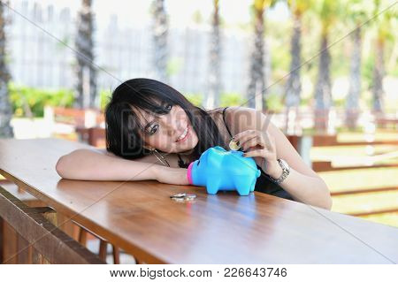 Business Concept. Beautiful Business Woman Saving Money In A Piggy Bank. Beautiful Businesswoman Loo