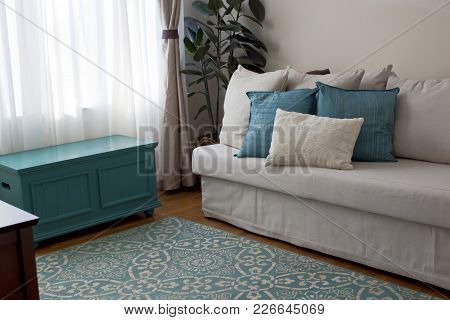 A Living Room With A Couch, Pillows, Chest, Drapes And Rug With Teal & Cream Color Scheme.