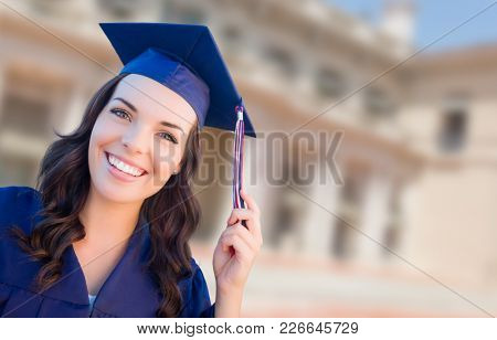 Happy Graduating Mixed Race Woman In Cap and Gown Celebrating on Campus.