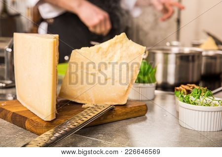 Grated Parmesan Cheese And Metal Grater On Wooden Board With Greenery In The Kitchen