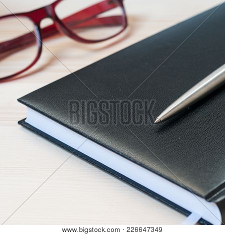 Agenda, Pen And Glasses  On A Wooden Table. Office And Management Concept. Selective Focus On The Ba