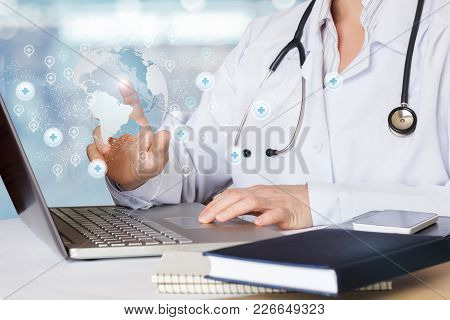 Doctor Working In The Internet At The Table.