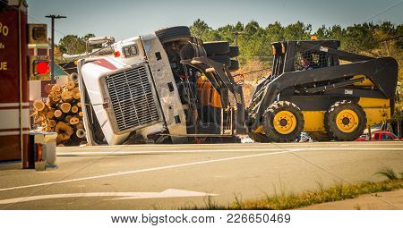 Overturned Logging Truck With Workers On Road