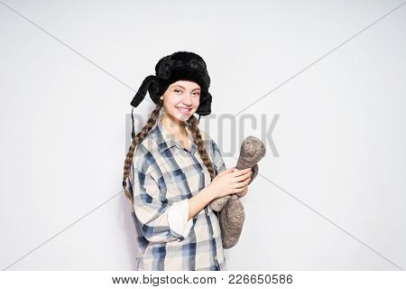Happy Young Russian Girl In A Black Hat With Ear-flaps Thinking About Russia, Holding Felt Boots