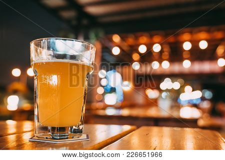 One Pint Of Beer On Restaurant Table With Copy Space On Blur Bokeh Background. Happy Event Celebrati