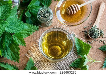 A Cup Of Nettle Tea With Fresh And Dry Stinging Nettles In The Background, Top View