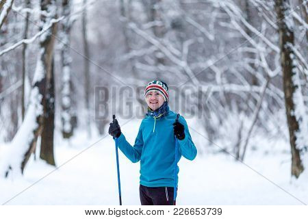 Portrait Of Male Skier In Forest At Winter Afternoon