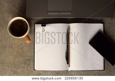 Grey Brown Grunge Table With Laptop, Coffee Cup, Clip, Notebook, Pen, Penclil. Top View With Copy Sp