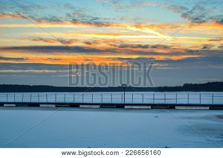 Afternoon Winter Landscape. A Pier Over A Beautiful Frozen Lake.