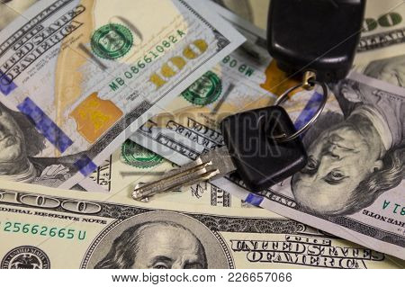 Key With Car Key Ring On Background Of  American One Hundred Dollar Bill