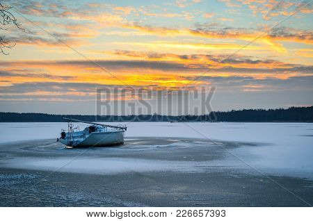 Afternoon Winter Landscape. Boat On A Frozen Lake.