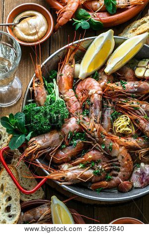 Roasted Prawns Shrimps In A Pan With Lemons, Bread And Wive.