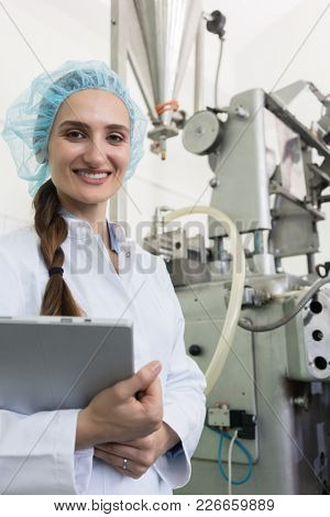 Portrait of a quality control female inspector smiling and looking at camera while holding a tablet during inspection in a contemporary cosmetics factory