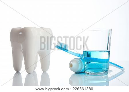 Toothbrush, Toothpaste, Dental Mouthwash And White Tooth Model Isolated On White Background, Close-u