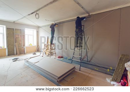 Workers Are Installing Plasterboard (drywall) For Gypsum Walls In Apartment Is Under Construction, R