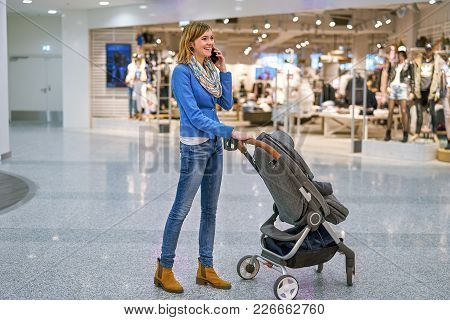 Young Beautiful Woman Staying With Pram In Front Of Clothing Store And Speaking On Mobile Phone