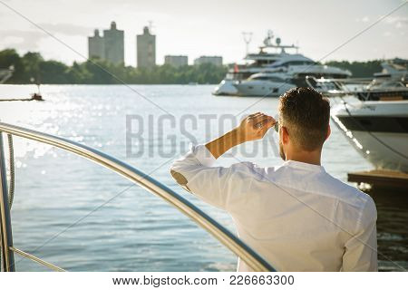 Rear View Of A Powerful Businessman Standing By Expensive Sailing Boats And Yachts In A Coastal City