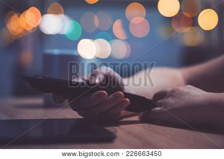 Female Hand With Television Remote Control Pointing To Tv Set And Turning It On Or Off Or Changing C