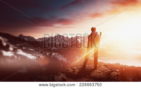 Hiker standing on a rocky mountain summit watching the golden glow of the rising sun at dawn over a winter landscape of snowy mountain peaks and valleys in an atmospheric panorama