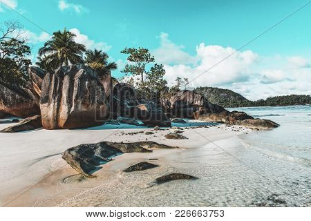 Idyllic tropical island beach with a large rock formation and palm trees and the calm ocean lapping gently on golden sand in a travel concept