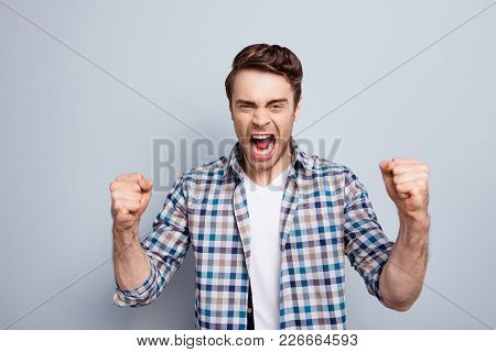 Aggressive Man In Checkered Shirt With Raised Fists And Open Mouth Is Out Of Himself, Yelling, Screa