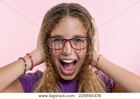Teen Girl With Glasses, With Long Hair Scratches Her Head And Is Emotional Puzzled. Pink Studio Back