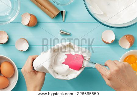Female Hands Filling Confectionary Bag With Whipped Egg Whites Cream On Blue Wooden Backround. Step