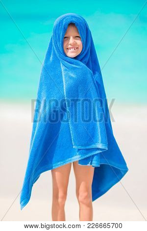 Adorable Girl Wrapped In Towel At Tropical Beach After Swimming In The Sea