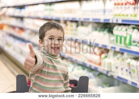 Happy Boy 4 Years In A Supermarket On The Background Of Shelves With Milk And Yogurt.