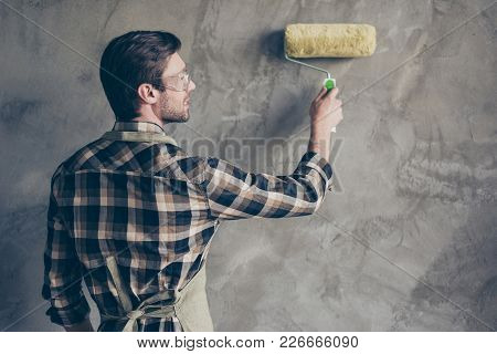 Rear View Of Young Man With Stylish Hair Do, Is Working With Paint Roller, Copy Space Near. He Is Sm