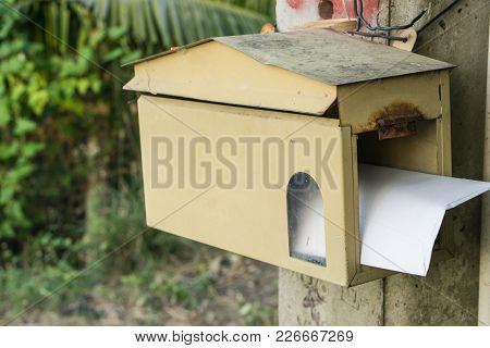 A House Shape Wooden Mailbox Hanging On A Tree With A Street (road) And A House Background. Old Comm