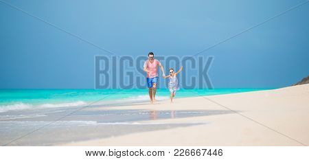 Happy Father And Adorable Little Daughter At Tropical Beach Having Fun